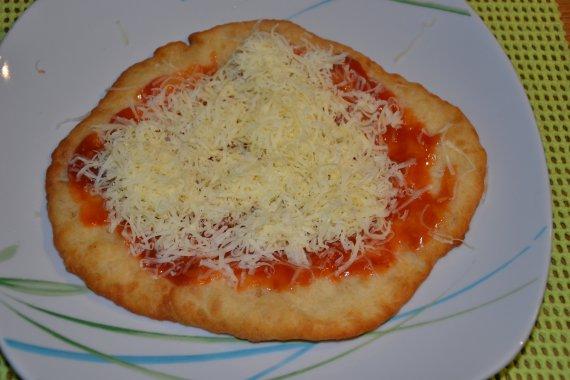Upečený Langoš potřeme česnekem, kečupem a posypeme sýrem. Co dodat? DOBROU CHUŤ!