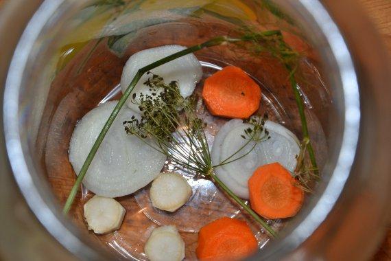 Na dno 2l sklenice dáme kopr a na kolečka nakrájenou cibuli, mrkev a petržel. Kolik? No přece přiměřeně! :-)