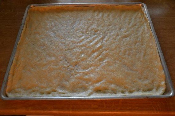Vykynuté těsto opatrně rozprostřeme na plech. Plech už vymazávat nemusíme. Zbytek rozpuštěného másla použijeme k potírání povrchu těsta, aby se nám nelepilo na ruce.